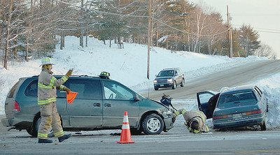 One firefighter investigates the damage to the minivan, while the other directs traffic on Rt. 1 the afternoon of Jan. 21. (E. Elliott photo)