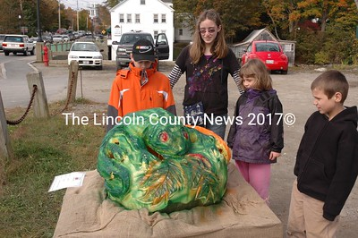 Joshua Meserve Jr (left) and sister Miranda, Ann Teele and her brother Austin are a bit perplexed with the Lizard coming out of his shell pumpkin. (Joe Gelarden photo)