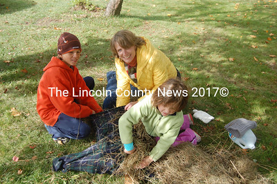 The Souzas make their unique scarecrow Saturday in front of the Wiscasset municipal building. From left, J.D., Stacey, and Lily Souza. (Greg Foster photo)