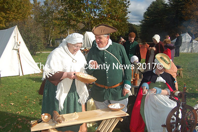 Wiscasset residents Deborah and Karl Olson examine preparations for pie cooked over an open fire at the colonial re-enactment at Pownalborough Courthouse in Dresden on Saturday. Their daughter Hannah, right, spins yarn. (Greg Foster photo)