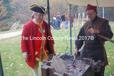 Forging metal for the King's troops gives Waldoboro blacksmith Jeff Miller an opportunity to demonstrate his skills for British officer Gus Konitsky of McGaffery's Creek Resources, which heads colonial re-enactments throughout the state. (Greg Foster photo)