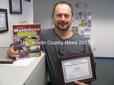 "Waldoboro Administrative Assistant Michael Ducharme proudly displays the award given to the town of Waldoboro from the Maine Municipal Association. Awards are presented to the top three town reports in their population group each year. Since the town of Waldoboro has a population of roughly 5000 residents, they are placed in the larger town category, competing with towns such as Bangor and Portland. Waldoboro placed second and this year's town report was determined to be of ""superior"" quality. Town Manager William Post gave Ducharme much of the credit for his work in putting the reports together. Waldoboro has won MMA awards for the past several years and last year placed first. (J Maguire photo)"