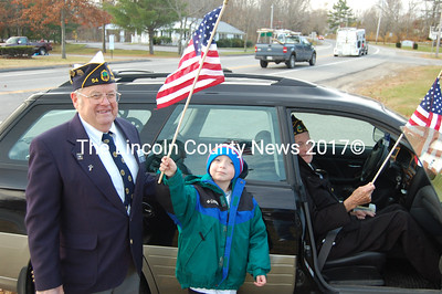 Oldest and youngest citizens at Wiscasset's Veterans' Day observance receive a flag from James Seigars, Sr., left, local American Legion Post commander. From left, Seigars, his great grandson Xavier Seigars, and John Sutter, World War II veteran. (Greg Foster photo)
