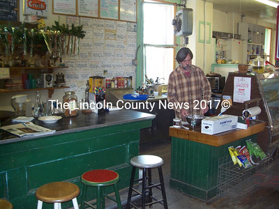 Sumner Richards makes frosting at Ferald's Country Store in downtown Waldoboro. He's preparing to host the 19th annual Christmas party on Christmas Eve, the last in the Waldoboro location. (Samuel J. Baldwin)