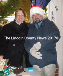 The wrapping duo of Mary Kate Reny and Greg Latimer, an erstwhile Santa, on Christmas Eve during the Damariscotta Street Festival. (S.Olin photo)