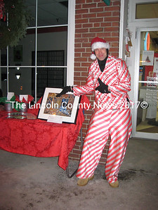 "Dressed as a candy cane, Core Redonnet said, ""See Dees?"" actually meaning he's selling CDs to benefit the Damariscotta Baptist Church Steeple Fund at the Damariscotta Street Festival. (S. Olin photo)"