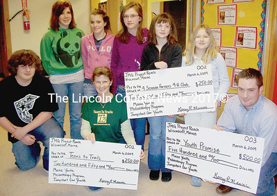 Wiscasset Middle School students spread the joy to three area non-profits with checks totalling $1000. Rear, from left, John Rines, Shelby MacPhee, Karianne Sprague, Kasey Cromwell, Allison Wehrle, and Samantha Arsenault. Front, Carol Leone of Teens to Trails and Steven McDermott of Youth Promise. (Greg Foster photo)