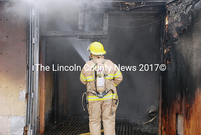 A Bristol firefighter soaks down the inside of the kiln to be sure the fire is completely extinguished. (E. Elliott photo)
