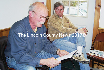Westport Island conservation commission chairman Bill Hopkins, left, seated with member Dennis Dunbar, reads a draft of comments listing concerns Westport Island has with the Riverbank Power Co. project during this week's selectmen's meeting. (Greg Foster photo)