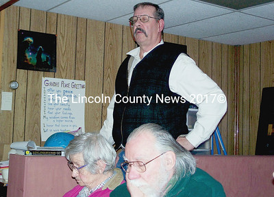 Edgecomb resident Sid Gammon, standing, speaks out for a town meeting vote on Wiscasset Public Library funding during the selectmen's meeting Monday. Jo and Bruce Cameron are in the foreground. (Greg Foster photo)