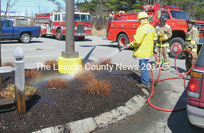 Damariscotta firefighter Dan Pinkham wets down  smoldering garden mulch at the Hannaford Supermarket on Monday. Fire Chief Neil Genthner Jr. said the dry mulch was ignited by a cigarette thrown down by a careless smoker. (Joe Gelarden photo)