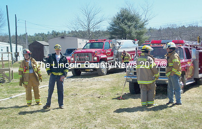Wiscasset fire department, and mutual aid departments  put out a woods fire Monday noon on Birch Point Road, which could have been a major blaze given the high winds, low moisture and a No. 57 on the fire hazard scale. Emergency management director Tim Pellerin, in background, was on the scene as well. (Greg Foster photo)