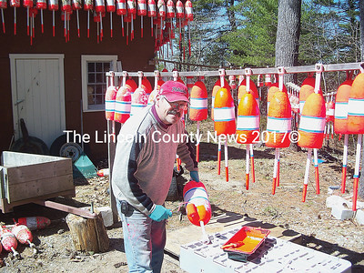 Westport Island lobsterman Mike Cromwell took advantage of the windy but sunny day Monday to repaint his buoys for the season. (Greg Foster photo)