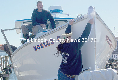 Lobsterboat owner Peter Fairfield of Wiscasst sits on the bow of his new vessel  before its launching and watches with excitement as his wife christens the Noelle G. (Greg Foster photo)