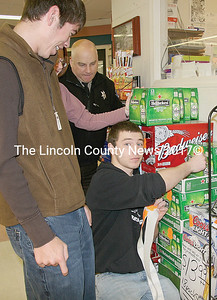 "Derek Juchnik, LA wrestling captain, sticks a case of beer with a warning label in Yellowfront grocery store in Damariscotta on Tuesday as a fellow classmate looks on. ""Project Sticker Shock"" students are visiting stores in various locations througout Lincoln County from April 7-10. (J Maguire photo)"