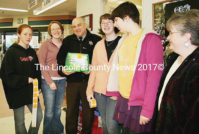 "Students and Lincoln County Sheriff's deputies are participating in ""Project Sticker Shock,"" a youth-led initiative to encourage adults not to purchase alcohol for minors. Posing with a stickered case of beer in Yellowfront Grocery store in Damariscotta are Deputy Mark Bridgham with Lincoln Academy student Sammy Spear (far left), partnership director for Healthy Lincoln County Rebecca Marin, LA students Jennifer Webster and Amelia Chambers and school nurse Ricky Waltz. (J Maguire photo)"