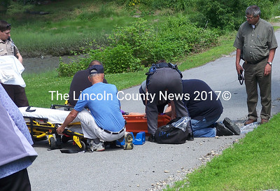 Responders prepare to lift an injured teen onto a stretcher for transport to Miles Memorial Hospital in Damariscotta. The youth apparently crashed while trying to ride a skateboard on Lewis Point Rd. He was not wearing a helmet. (Kim Fletcher photo)