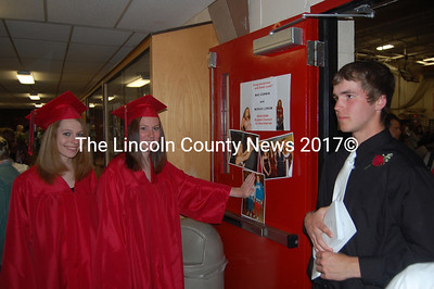 Wiscasset grads Laura Preble, left and Mariah Lorom laugh about their photos before graduation cermonies as Zack Pickering greets guests. (Greg Foster photo)