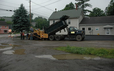 Paving day. Newcastle contractors take advantage of a temporary lull in the showers to pave the parking lot in front of the Newcastle town office. The paving followed the removal of an old septic tank. (Joe Gelarden  photo)
