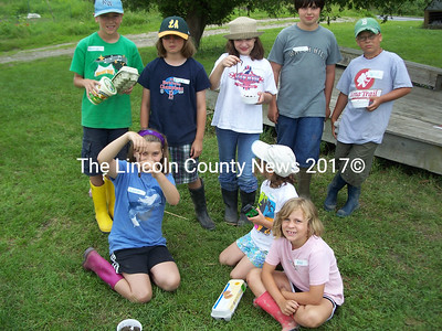 Youngsters proudly show worms they feed to chickens and prepare to collect eggs during Morris Farm's day farm camp. Front, from left, Lorin, Nora, and Avie. Rear, from left, George, Emma, Katherine, Michael, and Will. (Greg Foster photo)
