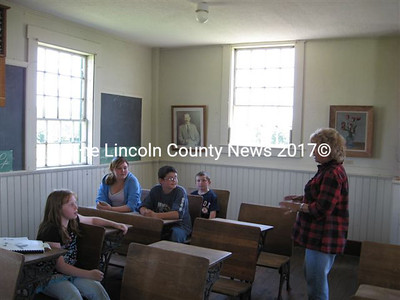 Volunteer guide Helen McKenzie tells visiting youth about the Center Schoolhouse on Saturday. On the wall at rear is a portrait of Pulitzer Prize winning poet Edwin Arlington Robinson, who was born in Head Tide Village in 1896.