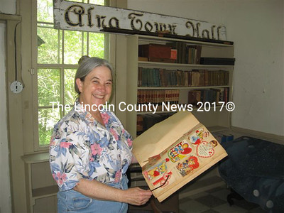 Mary McPherson, holding a scrapbook of Valentine cards from Puddle Dock School students in 1951, welcomed visitors to the historic Alna building last Saturday. (Lucy Martin photos)