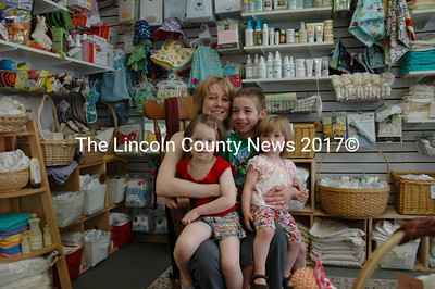 """Mom Christy Perce and her gang (from left): Audrey, 4, Kaden, 6, and Hanna, 1 in the family's newly relocated business """"The Baby Store"""" on Main Street Damariscotta. The store features natural baby friendly products including cloth diapers, natural  bottom cleaners and cute kid stuff. They also rent cribs and other baby gear for grandmas expecting tiny summer guests.(Joe Gelarden photo)"""