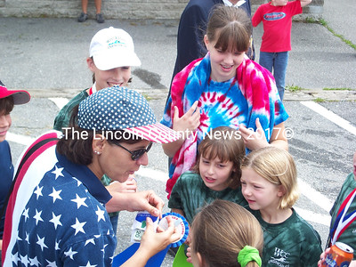 Swim instructor Lori  LaPointe shows members of Wiscasset Community Center Unsinkables the blue ribbon the team won for its float in the parade Saturday. (Greg Foster photo)