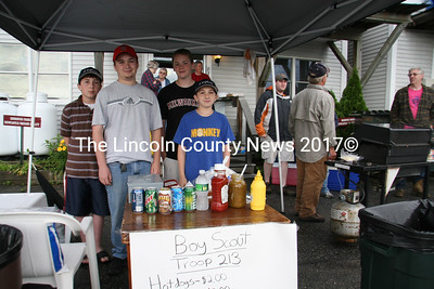 Boy Scouts Tom Kostenbader (center), Lucas Kostenbader (left), Grif Dodge (right) and Marshall Dodge sell hotdogs and other items to festival go-ers during July 4th in Damariscotta. (J Maguire photo)