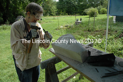 """Peg Brightman uses a hammer and chisel to carve out details on her """"thoughtful lady"""" sculpture. She says she thinks the lady is thinking about how she will pay her property taxes. (Joe Gelarden photo)"""