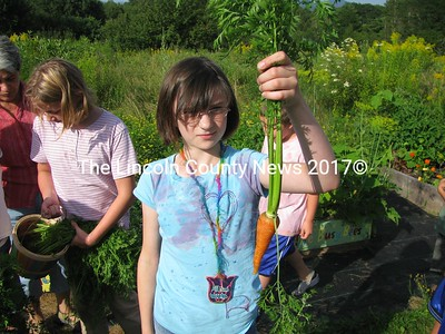 Kids Can Grow student gardener, Allison, proudly holds up one of the many vegetables she and fellow gardeners grew for local food banks. (J Maguire photo)