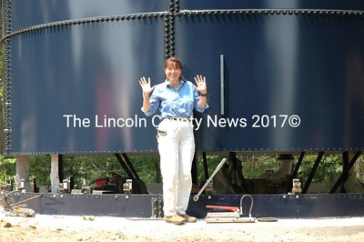 Hooray, its plumb.. Mary E. Bowers, the superintendent of the Great Salt Bay Water District puts a level to check a 143,000 gallon water storage tower being constructed on Standpipe Road not far from Little Pond. (Joe Gelarden photo)