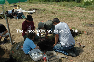 Neill DePaoli, (center in light hat) peers into a pit dug into a Bristol hayfield that was once the home of a Colonial era community leader and farmer. (Joe Gelarden photo)