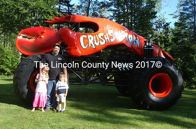 Greg Winchenbach builder, owner and driver of Crushstration and his children Ashley and Zachary are dwarfed by the size of the monster truck. (Paula Roberts photo)
