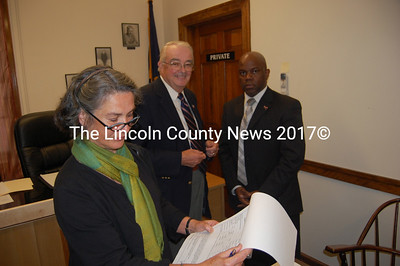 Midcoast Economic Development District board president Eloise Vitelli, left, looks over the federal Economic Development Administration planning funding papers for this fiscal year in the presence of Lincoln County Commissioner chairman Bill Blodgett, center, and Willie Taylor of the EDA. (Greg Foster photo)