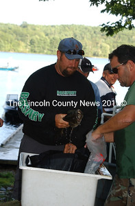 Joe Holland places his Sunday catch in a bag to be weighed at the Damariscotta Lake state boat launch in Jefferson on Sunday. Holland placed sixth in the Maine Bass Federation State tournament to qualify for Divisionals.