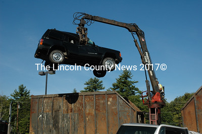 The executioner, Ed Bernard, hoists a Jeep into the air prior to stuffing it into the bin in his huge truck. The Jeep was one of 88 cars taken in at Wiscasset Ford as part of the Cash for Clunkers program. (Joe Gelarden photo) .
