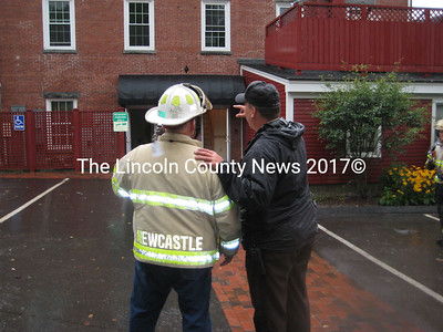 Newcastle Fire Chief Clayton Huntley and LCSO Lt. Rand Maker confer outside the Newcastle Publick House during a response to a chimney fire Saturday.