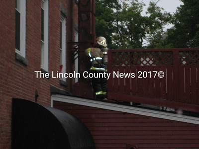 Newcastle fireman Bob Hatch inspects a chimney that caught fire outside the Newcastle Publick Square restaurant Saturday.