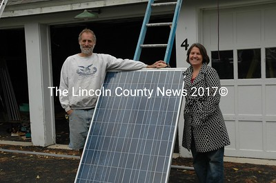 Richard Simon (left) and his partner, Susan Bickford and one of the solar panels he is installing on his garage roof in Newcastle. The unique system produces electricity from sunshine. Simon hopes to produce 50 percent of his home's electricity with the $17,000 system. (Joe Gelarden photo)