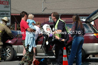 Paramedics carefully taped three-year-old Jacob to his baby seat then removed him from the wrecked car driven by his mother Amanda Spicer, 23. Paramedic Nate Powell carried the infant to the waiting ambulence. Spicer and three others were hospitalized in the three-car accident that too place Wednesday on Business Route 1 in front of Hancock Lumber in Damariscotta. Police said their injuries were not threatening.. (Joe Gelarden photo)