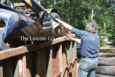 First Selectman Bob Blagden, contractor for cleanup of the former Lewis property places another junk item onto the dumpster. (Greg Foster photo)
