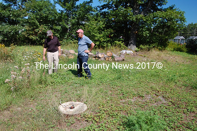 Wiscasset Town Manager Arthur Faucher and code enforcement officer Rick Lang inspect the pipe for an underground oil tank where possible contamination could occur on the Koehling property. (Greg Foster photo)