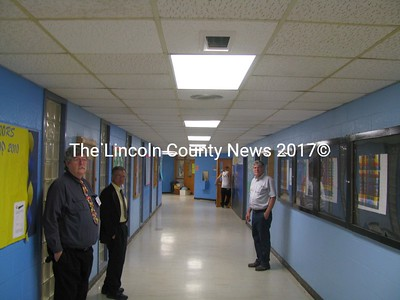 The dark box protruding from a ceiling tile (top center) is a video camera. There are several throughout the school property. Standing are RSU (MSAD) 40 business manager Scott Vaitones (right), supertintendent Frank Boynton (left front) and MVHS principal Harold Wilson. (J Maguire photo)