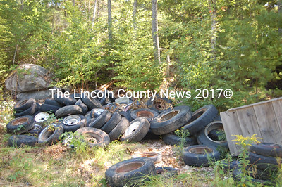 Tires piled up on the former Lewis property in  Wiscasset have to go in the cleanup operations Bob Blagden has been handling lately for the town. (Greg Foster photo)