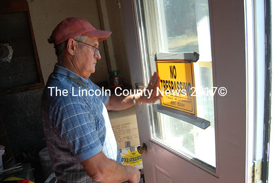 Wiscasset code enforcement officer Rick Lang places a no trespasssing sign on the house on Rt. 27 the town had to lock up per court order for non-payment of taxes. (Greg Foster photo)