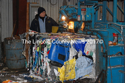 Bob Mooney runs the bailer at Lincoln County Recycling Friday afternoon. It wires up giant bales of processed rigid plastic and corrugated cardboard. Bales weigh an average 1500 pounds apiece. (J Maguire photo)