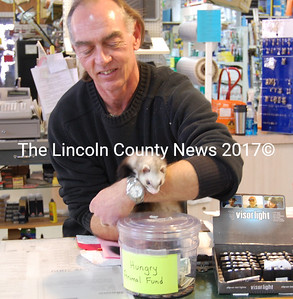 Rich Bewell at Louis Doe's Pet Center in Newcastle holds a ferret and shows off the hungry animal fund donation canister. The fund provides free pet food for animal owners in need. (Samuel J. Baldwin photo)