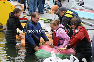Divers assist competitor Chelsea Pinkham into her watermelon inspired pumpkin craft during Damaroscottas Pumpkin Regatta Oct. 10. (Matthew Stilphen)