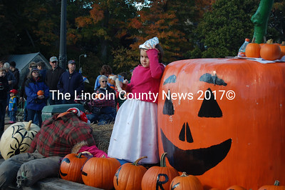 A young Clark's Farms employee helped her colleagues distribute pumpkins to the crowd. (J.W. Oliver photo)